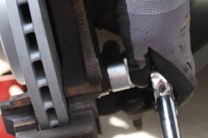 Der Steckschlüssel öffnet den Bremssattel an der Bremsenanlage